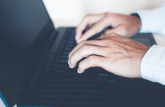 close-up of business man hand typing and using laptop keyboard for searching with technology networking on working and job on desk at work place or work at home.