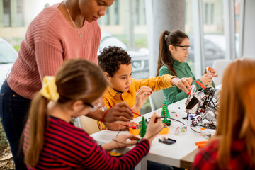 African American female science teacher with group of kids programming electric toys and robots at...