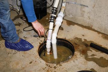 Fototapeta  A plumber repairing a sump pump in a flooded basement in a residential home