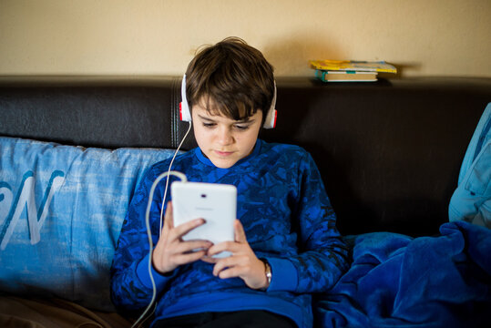 12 year old boy listens to music sitting on the sofa with tablet in hand