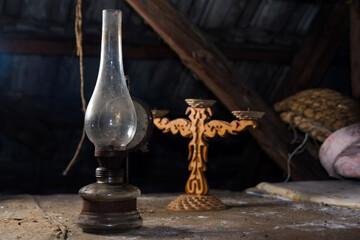 Obraz Stara lampa naftowa i świecznik na strychu - fototapety do salonu