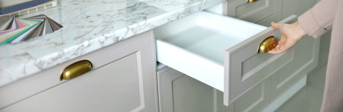 Banner Home improvement concept. young girl designer opens a drawer of a kitchen cabinet in a shop salon.