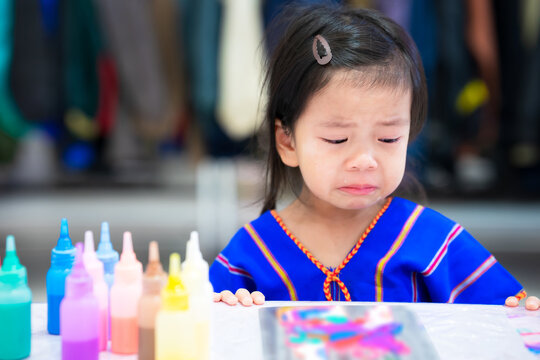 Sad child girl crying when there is a mistake in art work. Learning from mistakes. Accepting and correcting mistakes that have already occurred. Cute children 3-4 years old.