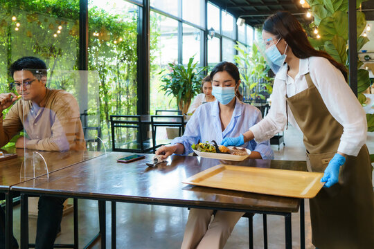 Asian woman waering mask and asian people eating food alone at table with plexi screen between table in reopening restaurant after lockdown measure.