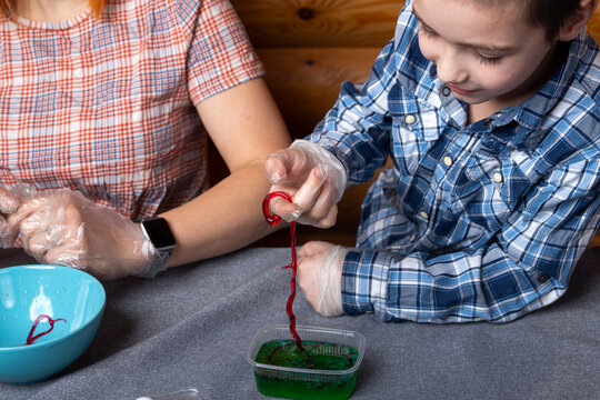 Chemical experiments with a child. Mom and her son make polymer worms at home