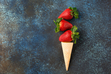 Fresh strawberries in waffle cones, healthy summer food concept, top view.