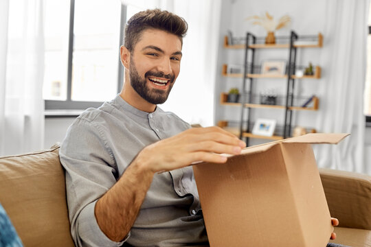 mail delivery, shipment and people concept - happy smiling man opening parcel box at home