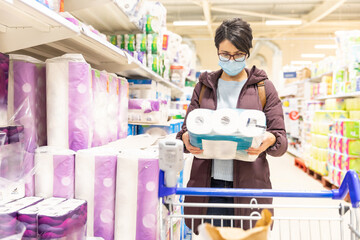 Woman buying toilet paper rolls at supermarket ahead of lockdown and wearing a face mask during...