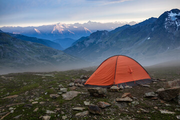 Base camp set in Alpine background. Ten set on hill i Alps mountains. Tourist shelter camp in high mountains.