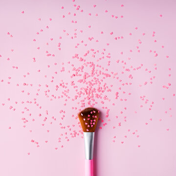 Make up brush with heart shaped glitter on pastel pink background. Minimal make up or glamour cosmetic salon concept. Flat lay, top view.