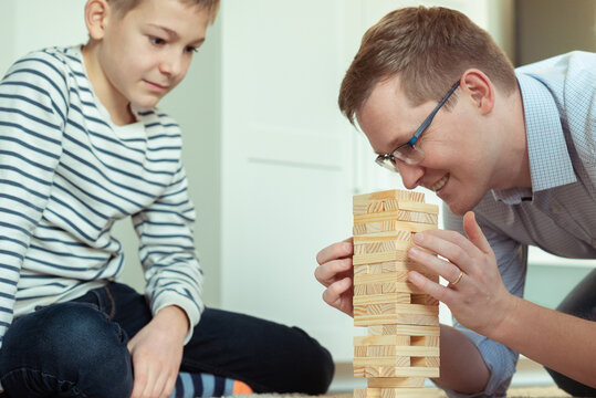 Happy father playing with cute son with wooden blocks at home