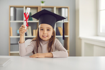 Education for children concept. Adorable preschool girl in academic cap looking at camera, holding...
