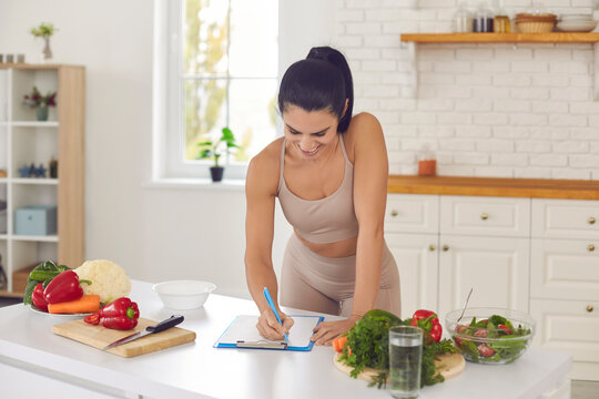Cheerful pretty slim female athete in sportswear standing in kitchen in sportswear and writing down healthy recipe or daily ration diet at home. Active healthy lifestyle, clean eating concept