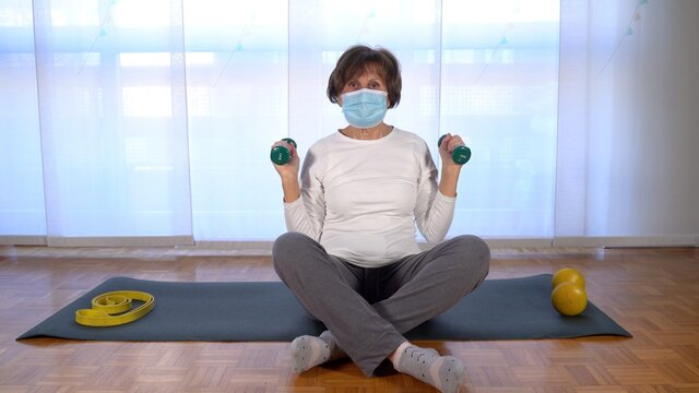 elderly lady does gymnastics in apartment during Covid-19 Coronavirus lockdown quarantine home - lifestyle during pandemic