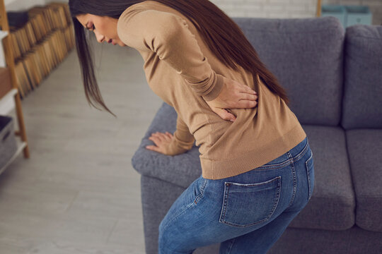 Woman feeling pain and touching lower back. Young lady suffering from backache, hurt muscles, injury, vertebral displacement, rheumatism, radiculitis, spine arthritis, or sudden pinched nerve attack
