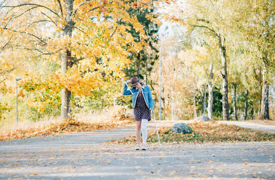 injured woman walking with crutches with the wind blowing in fall