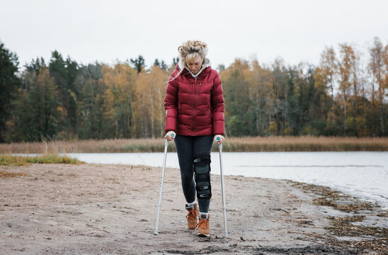 injured woman walking with crutches on the beach looking thoughtful