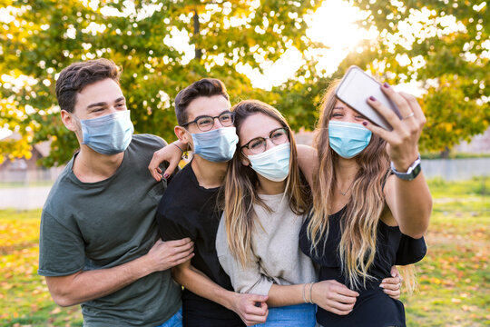 Teen group of friends together at park after school, wearing masks and taking a selfie - Lifestyle and friendship concepts during coronavirus pandemic