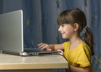 .Distance learning online education. A happy girl lookes at laptop and smiles