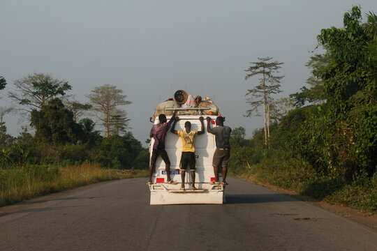 People ride on the back of a minibus on the road to the town of Soubre