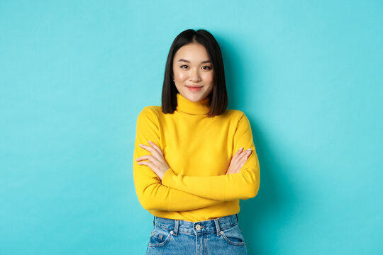 Attractive asian woman with short dark hair, cross arms on chest and smiling confident, standing over blue background