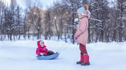 Happy girl enjoying a sleigh ride. Child sledding. Toddler kid riding a sledge. Elder girl pulling a smiling girl on sledge. Children play outdoors together.  Outdoor fun for family winter vacation.