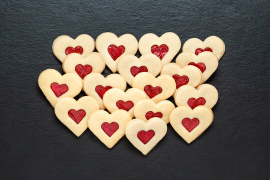 christmas cookies hearts with strawberry jam on slate table