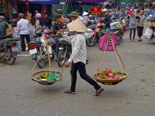 Fototapeta Full Length Of Vendor Selling Fruits On Carrying Pole At Street In City obraz