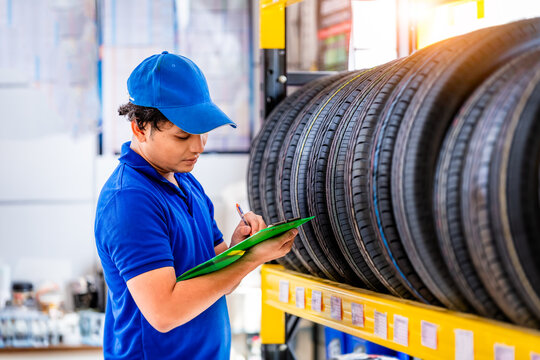 Car Mechanics check quality tire of car wheels in store warehouse for customer in garage ,car service.