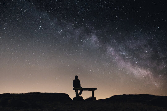 Silhouette of a person sitting on a bench in background of the magical starry sky