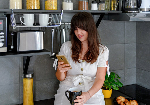 shot of female drinking from a mug while using her mobile phone in the kitchen