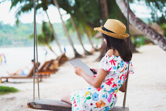 Young girl sitting on swing on the beach using digital tablet