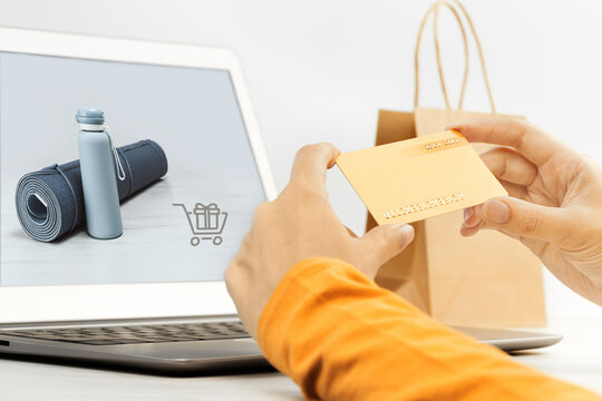 Woman shopping. online sports sale holding a gold credit card in hands. e-commerce and seasonal sale, shopping from home during lockdown or remote working browsing internet. Laptop. delivery service