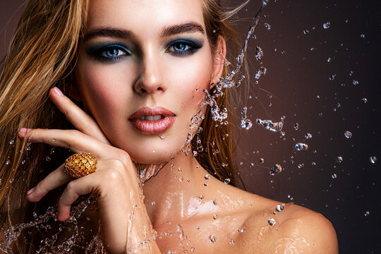 Photo of young woman with style make-up and water splashes  . Portrait of blonde woman with drops of water around her face. Sexy girl with blue eye makeup. Fashion model and water.