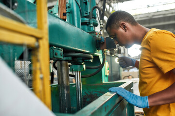 Fototapeta Young man managing compression machine on waste station