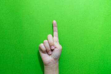 Cropped Hand Of Child Gesturing Against Green Background