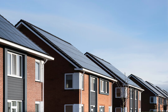 Solar panels mounted on the roofs of a row modern new-build houses in Lemmer, Friesland, the Netherlands with blue sky