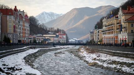 The Mzymta river in the Krasnaya Polyana resort. Tourists walk along the embankment Fotobehang
