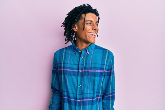 Young african american man wearing casual clothes looking away to side with smile on face, natural expression. laughing confident.