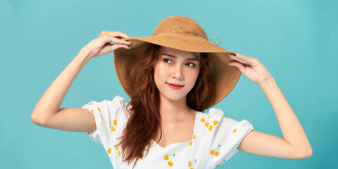 Cool woman wearing summer hat looking at camera and smiling, posing on blue studio background.