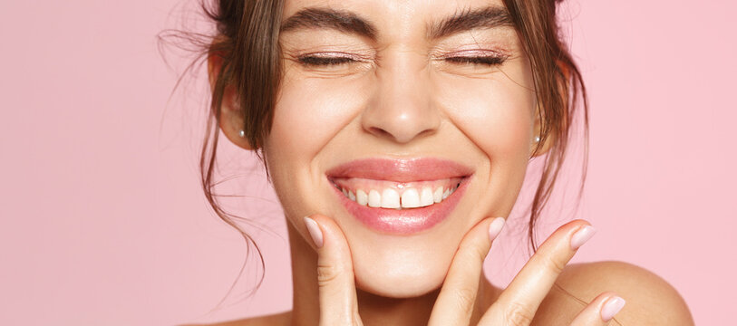 Close up of happy young woman with fresh glowing skin tone, showing beautiful white smile and grinning carefree, happy about valentines day, standing on pink background