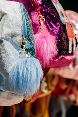 Wall Murals Carnaval Selective focus vertical shot of bags with pompoms. Colorful bags in the market