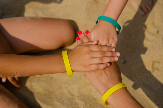 Family wearing color entrance wristbands of hotel resort or entertainment park at sand sea background.