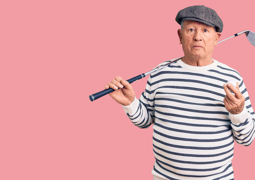 Senior handsome grey-haired man holding golf club and ball thinking attitude and sober expression looking self confident