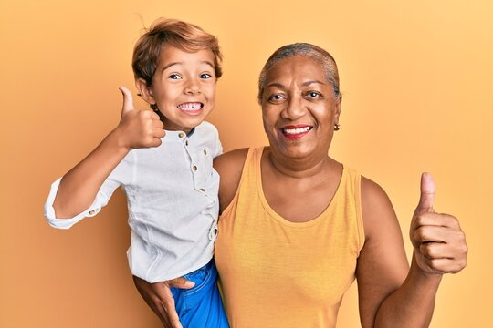 Hispanic grandson and grandmother together over yellow background smiling happy and positive, thumb up doing excellent and approval sign