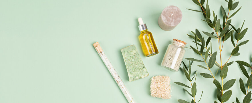 Cosmetics branding mockup. Bottles of eucalyptus essential oil, soap bar, fresh eucalyptus branches on green background. Natual organic ingredients for cosmetics, skin care, body treatment