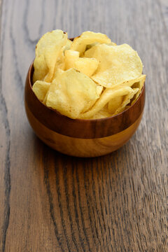 Wood bowl of crispy Kettle potato chips on a hardwood plank