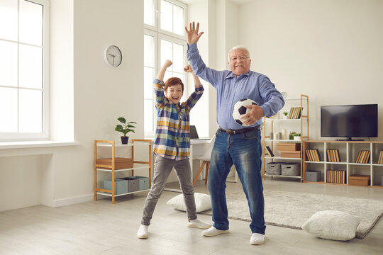 Free time, happy childhood and active senior's lifestyle: Cheerful grandfather and teen grandson having fun together, playing sports games at home and celebrating victory of favorite soccer team