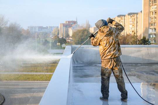 Photography of roof cleaner in yellow uniform. He is washing top of building from dirt. Cityscape is visible in the background.