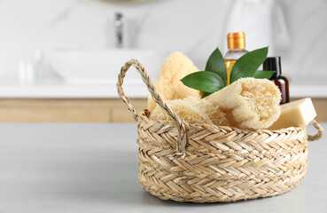 Wall Mural - Natural loofah sponges in wicker basket on table indoors. Space for text